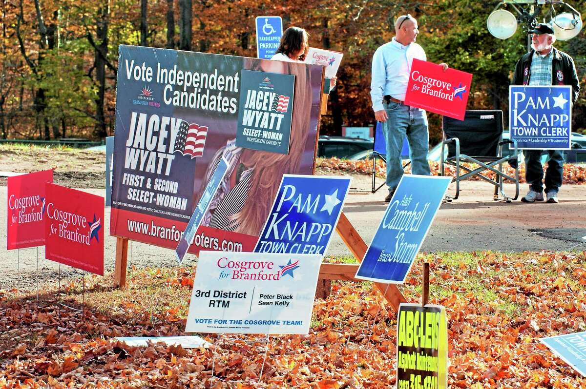 Hunter Kelly, Sean Kelly and Ted Aub hold signs promoting their favored canddiates in front of the 3rd Voting District in Branford Tuesday.