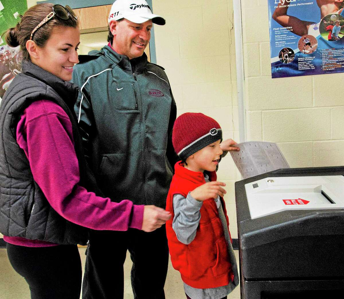 Rocco DeMaio III helps his parents, Karla and Rocco Jr., cast their ballots at Sheriden Middle School in New Haven Tuesday.