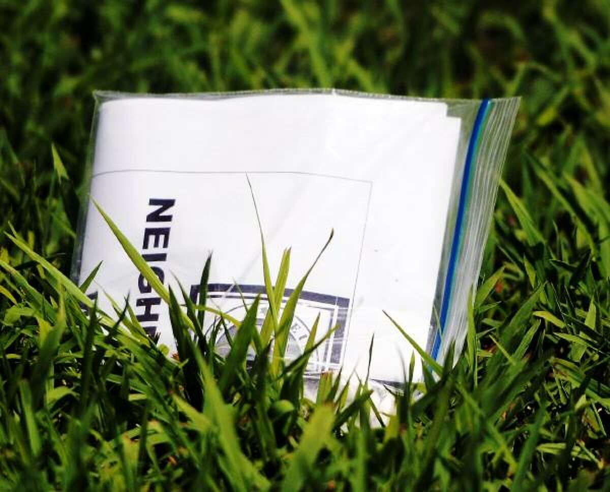 Peter Hvizdak/New Haven Register Printed material in a plastic bag on the front lawn at 181 Herbert Avenue in Milford, Connecticut July 9, 2013.