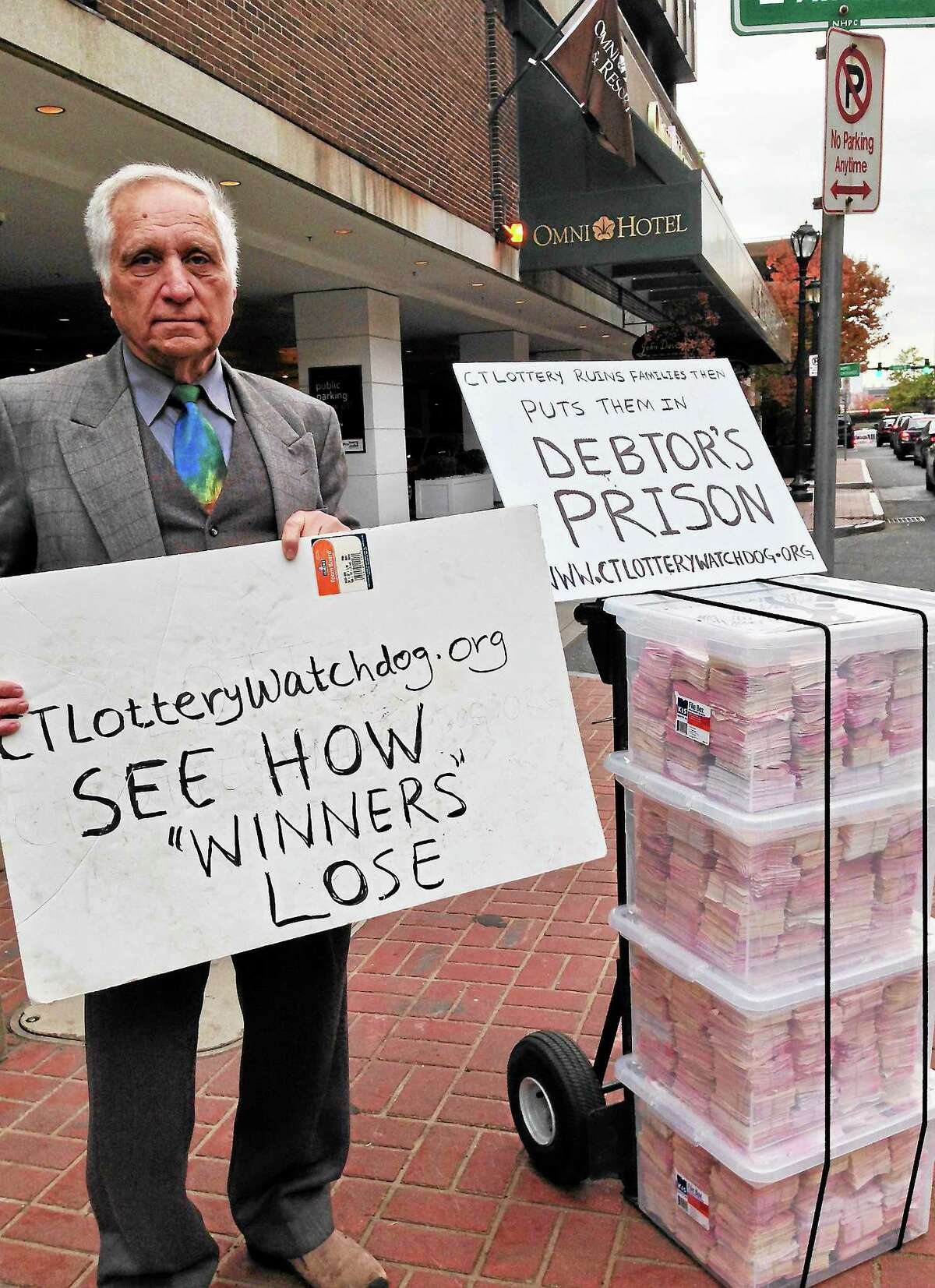 Charlie Merlis of West Hartford mans Adam Osmond's lottery protest, with thousands of losing tickets, outside the CCPG conference in New Haven Wednesday morning. Osmond declined to be photographed.