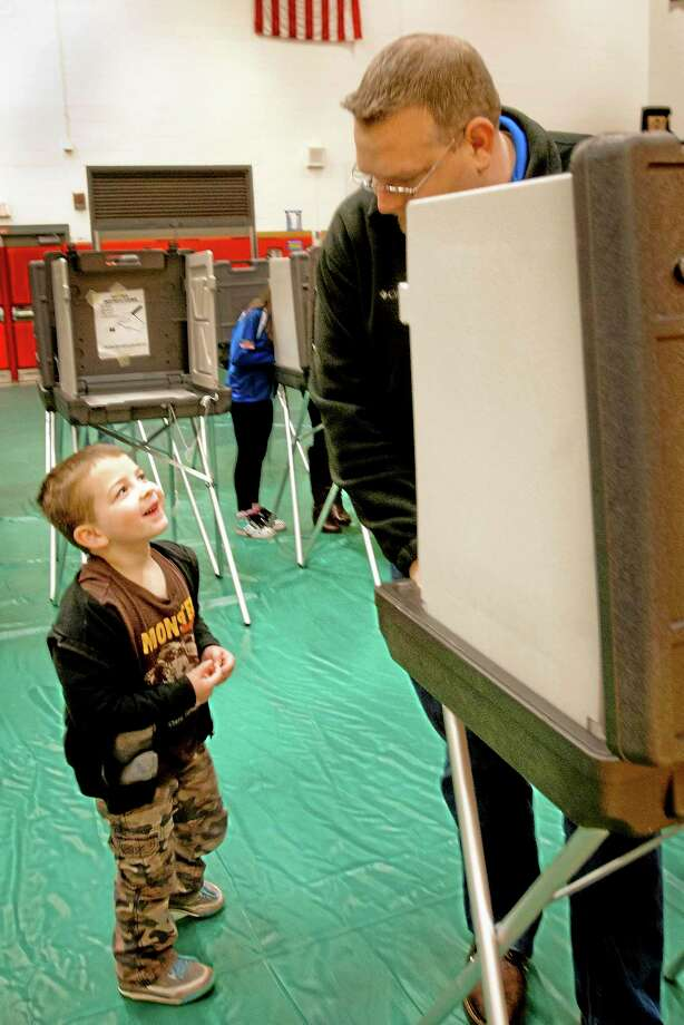 Jake Chikowski gets a civics lesson from his father, Joseph Chikowski, as the elder Chikowski votes at Foran High School in Milford Tuesday. Photo: Melanie Stengel — New Haven Register