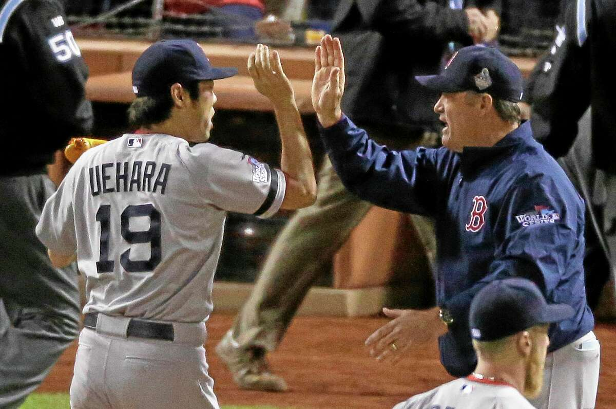 Boston Red Sox manager John Farrell congratulates relief pitcher Koji Uehara after Boston defeated the St. Louis Cardinals in Game 5 of the World Series 3-1 to take a 3-2 lead in the series.
