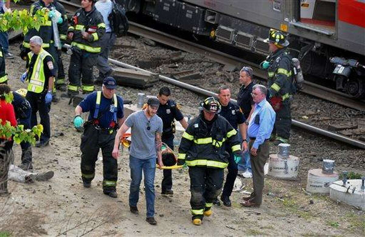 Injured passengers are transported from the scene where two Metro North commuter trains collided, Friday, May 17, 2013 near Fairfield, Conn. Bill Kaempffer, a spokesman for Bridgeport public safety, told The Associated Press approximately 49 people were injured, including four with serious injuries. About 250 people were on board the two trains, he said. (AP Photo/The Connecticut Post, Christian Abraham)