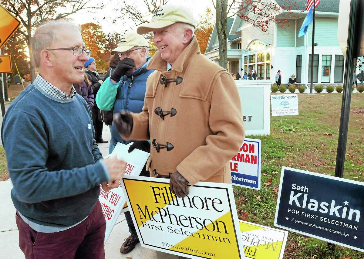 Voter Dennis Van Liew, left, speaks with Madison First Selectman Fillmore McPherson outside the Madison Senior Center polling place Tuesday.