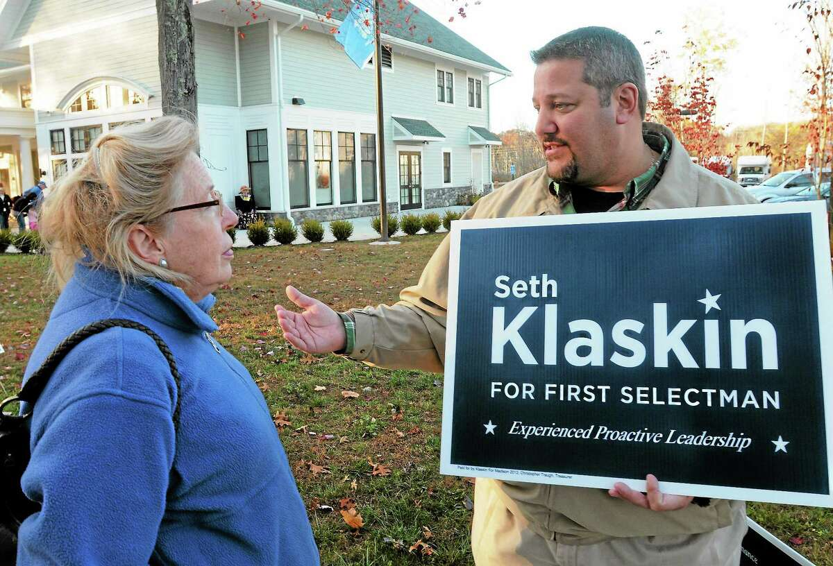 Voter Judith Young, left, asks questions of Madison first selectman candidate Seth Klaskin outside the Madison Senior Center polling place Tuesday.