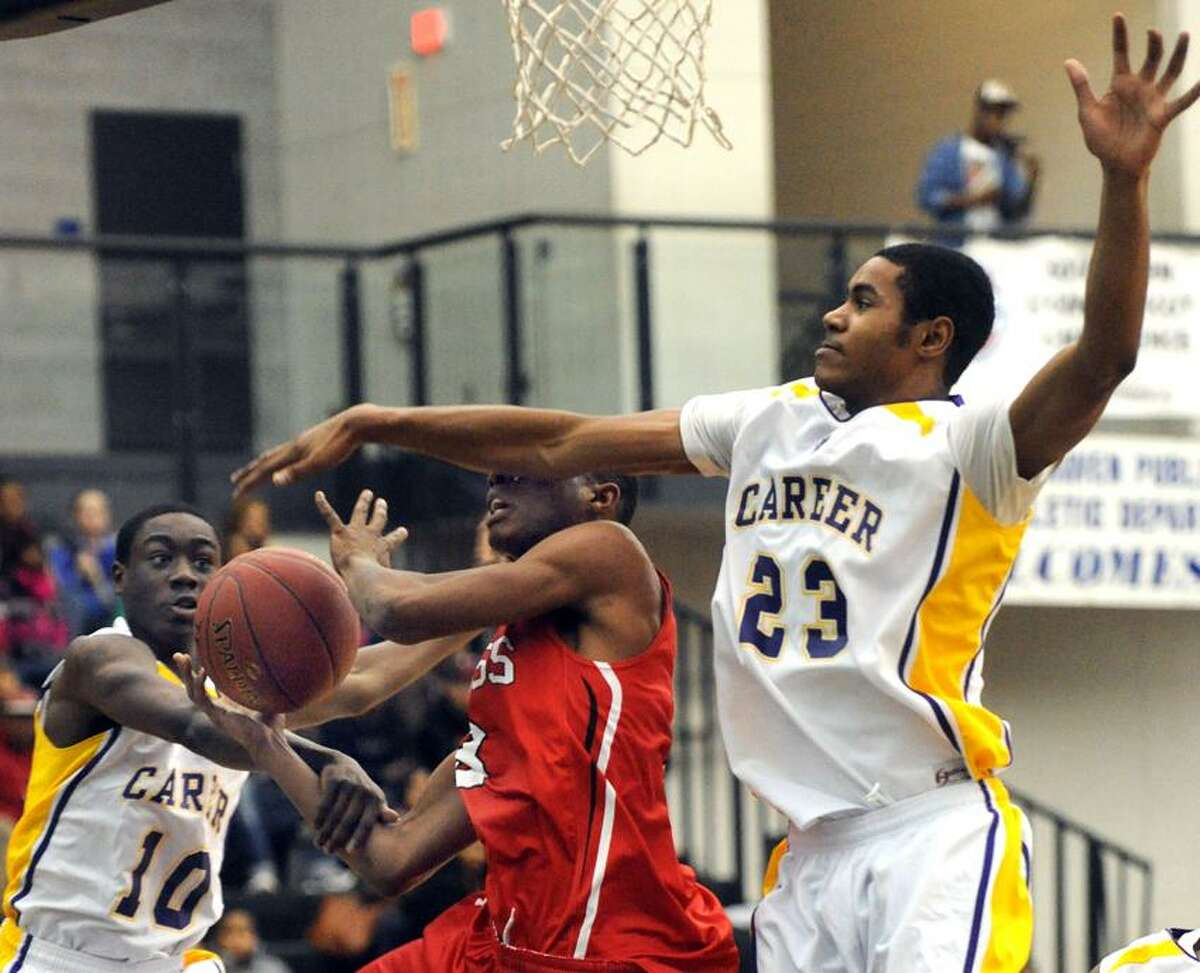 Career vs. Wilbur Cross at the Floyd Little Athletic Center, New Haven. Career's Tyrell Eaddy left and Justin Campbell as Campbell fouls Cross' Michael Judkins. Mara Lavitt/New Haven Register1/17/13