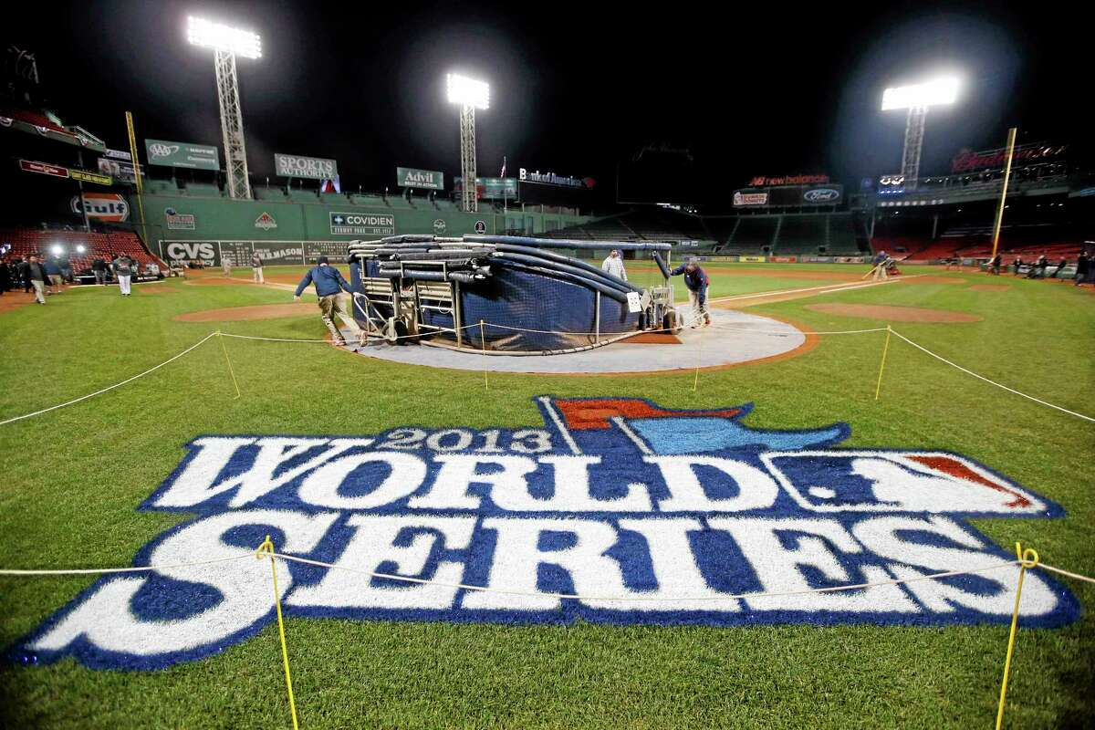 Grounds crew members dismantle the batting cage after the Red Sox's workout on Tuesday at Fenway Park in Boston. The Red Sox host the St. Louis Cardinals in Game 6 of the World Series on Wednesday.
