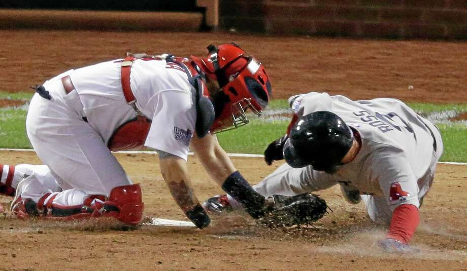 Cardinals catcher Yadier Molina tags out the Boston Red Sox's David Ross during the seventh inning of Game 5 of the World Series on Monday in St. Louis. On Tuesday, Molina won his sixth consecutive Gold Glove. Photo: Charlie Riedel — The Associated Press   / AP