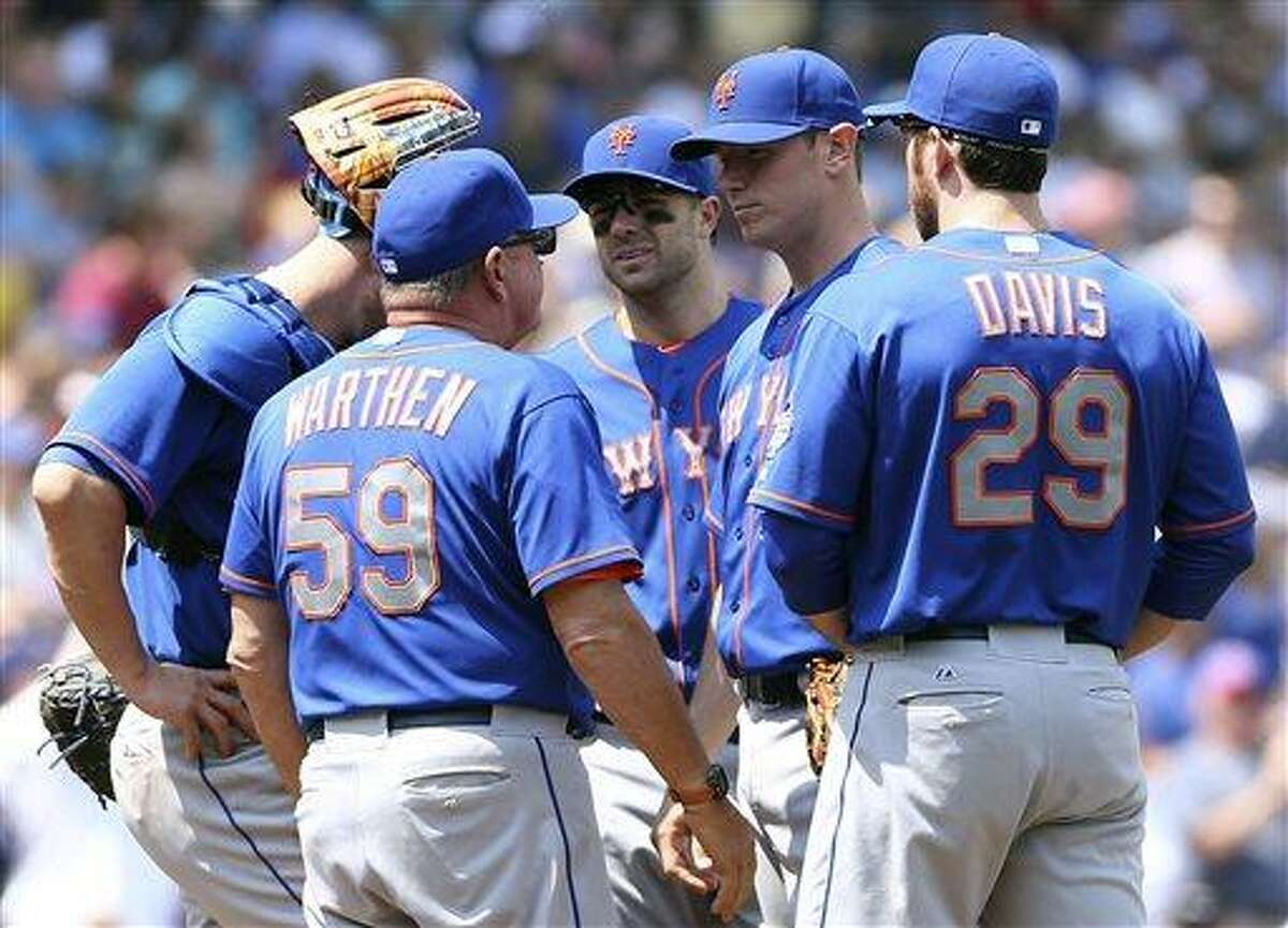 New York Mets pitching coach Dan Warthen has a meeting on the mound after starting pitcher Jeremy Hefner, second from right, gave up four runs in the fourth inning of a baseball game against the Chicago Cubs Saturday, May 18, 2013, in Chicago. Other players on the mound are, from left, John Buck, David Wright and Ike Davi . (AP Photo/Charles Cherney)