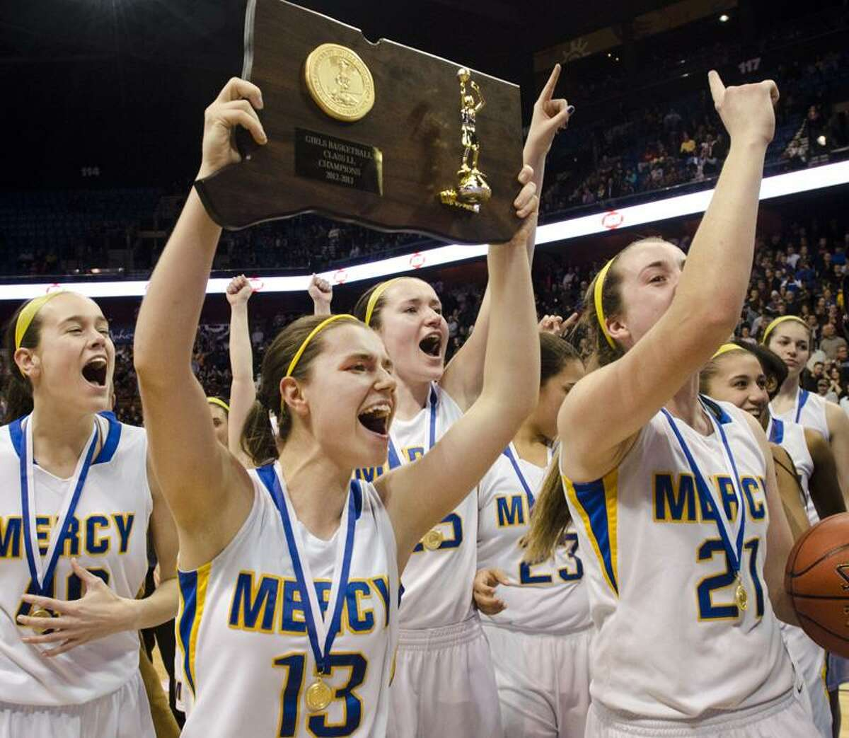 Members of the Mercy girls' basketball team celebrate after beating Lauralton Hall to win the Class LL championship on Saturday at Mohegan Sun Arena. (Melanie Stengel/Register)