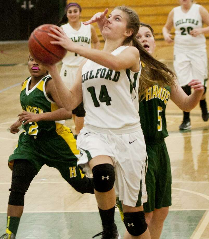 Guilford's Caroline Miller escapes the long arm of Hamden's Quiessence Rock during the third quarter of Guilford's 52-34 win Thursday night.   Melanie Stengel/Register.
