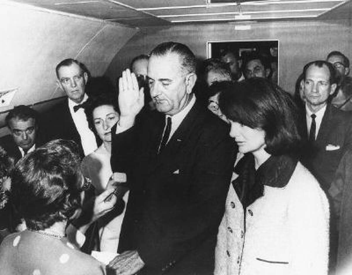 Flanked by Jackie Kennedy (R) and his wife Lady Bird Johnson (2ndL), U.S Vice President Lyndon Johnson (C) is administred the oath of office by Federal Judge Sarah Hughes (L) as he assumed the presidency of the U.S., 22 November 1963, following the assassination of President John F. Kennedy.
