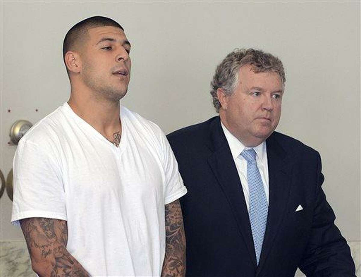 FILE - In this June 26, 2013, file photo, Aaron Hernandez, left, stands with his attorney, Michael Fee, right, during arraignment in Attleboro District Court in Attleboro, Mass. Since Hernandez was arrested last week in the shooting death of a friend whose body was found a mile away from his home, a portrait has emerged of a man whose life away from the field included frequent connections with police-related incidents that started as long ago as his freshman year at the University of Florida. (AP Photo/The Sun Chronicle, Mike George, Pool)