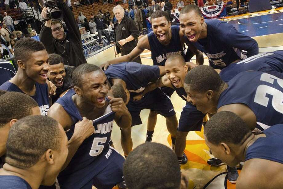 Sports- Marcus Brown, of Hillhouse  leads a chant in the huddle after the team beat Fairfield Prep in the e CIAC State Basketball Finals.   Melanie Stengel/Register