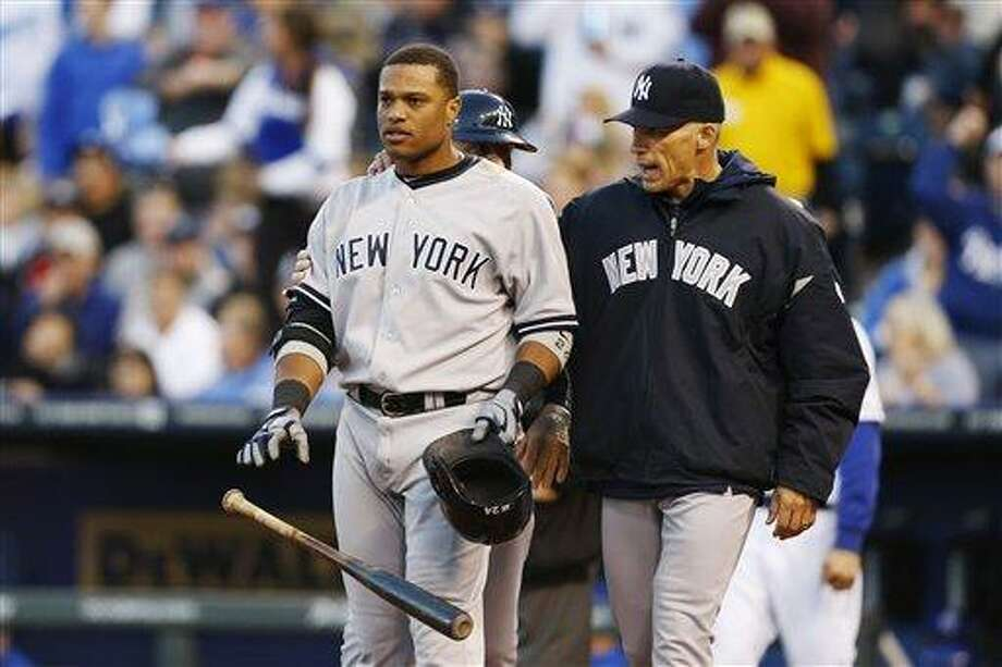 New York Yankees manager Joe Girardi, right, calms Robinson Cano (24) after he was called out on strikes during the seventh inning of a baseball game against the Kansas City Royals at Kauffman Stadium in Kansas City, Mo., Saturday, May 11, 2013. (AP Photo/Orlin Wagner) Photo: AP / AP