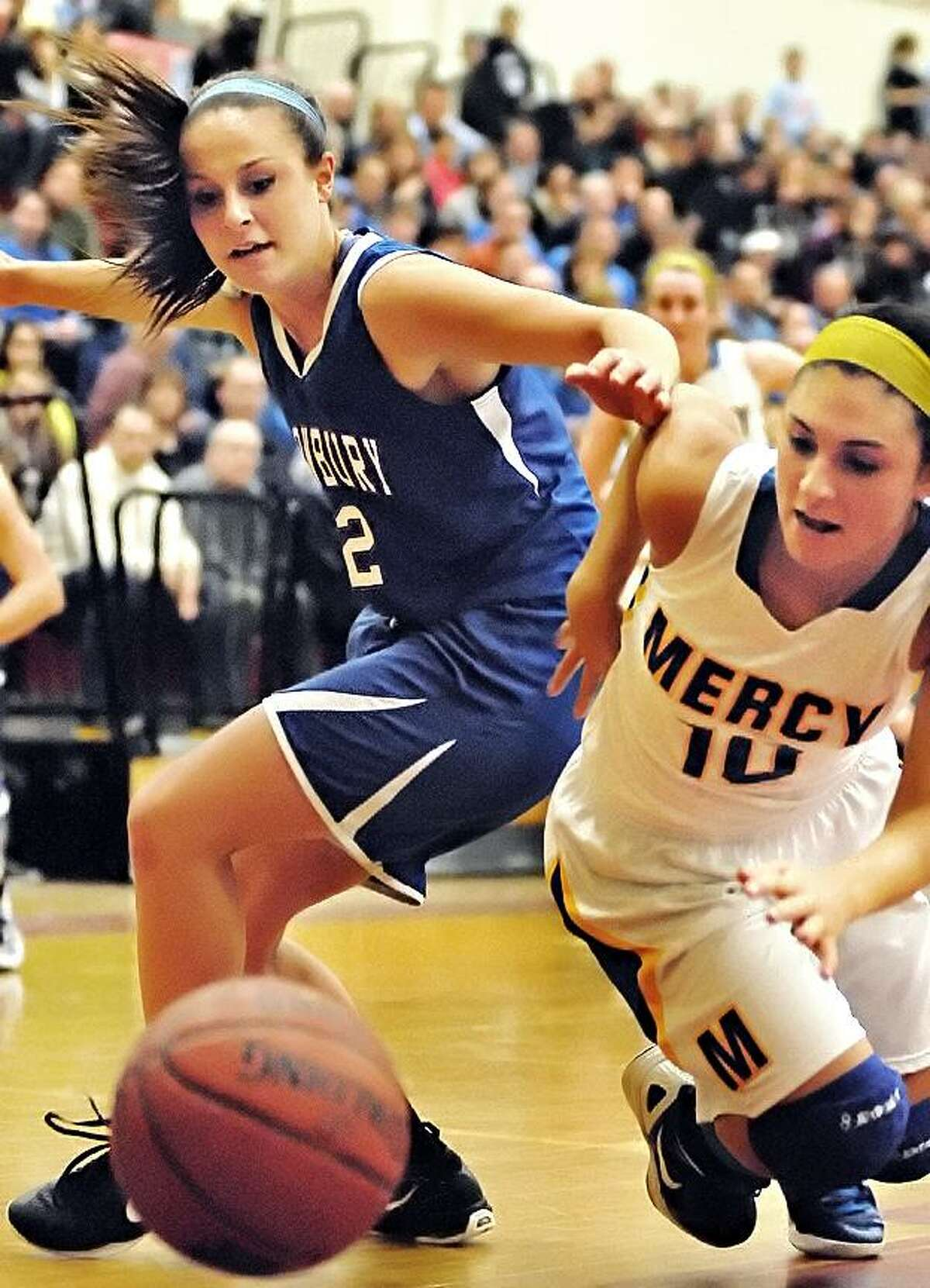 Catherine Avalone/The Middletown PressMercy senior Jordyn Nappi battles Glastonbury senior Katherne Nuzzolo for a loose ball in the second half of the Class LL Semifinal game. Mercy's46-43 win over Glastonbury in the CIAC Class LL at New Britain High School earns the Tigers their fourth consecutive appearance in the championship game this weekend at Mohegan Sun this weekend.