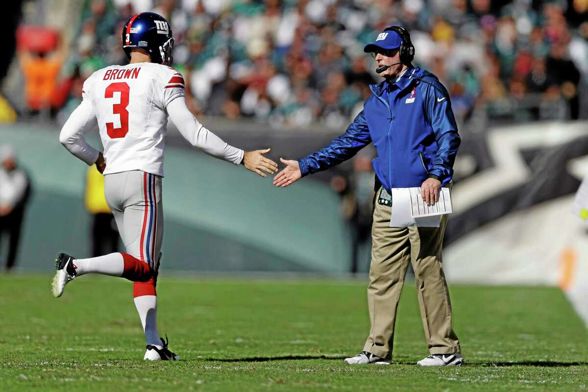 Giants kicker Josh Brown (3) low-fives by head coach Tom Coughlin after a field goal against the Eagles.