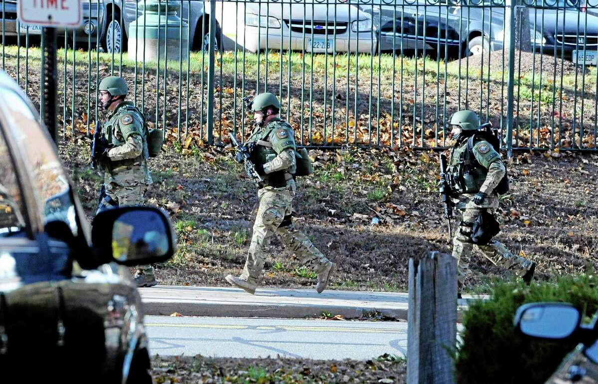 SWAT run in a line on the campus of Central Connecticut State University, Monday, Nov. 4, 2013, in New Britain, Conn. An armed man was spotted on the campus of Central Connecticut State University, prompting a schoolwide lockdown and warnings for students to stay away from windows as police SWAT teams swarmed the area. University spokesman Mark McLaughlin said,