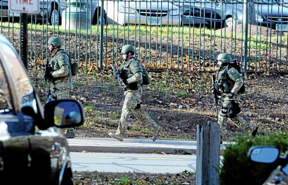 """SWAT run in a line on the campus of Central Connecticut State University, Monday, Nov. 4, 2013, in New Britain, Conn.  An armed man was spotted on the campus of Central Connecticut State University,  prompting a schoolwide lockdown and warnings for students to stay away from windows as police SWAT teams swarmed the area.  University spokesman Mark McLaughlin said, """"Somebody was seen either with a gun or was thought to have a gun."""" (AP Photo/Jessica Hill) Photo: AP / FR125654 AP"""