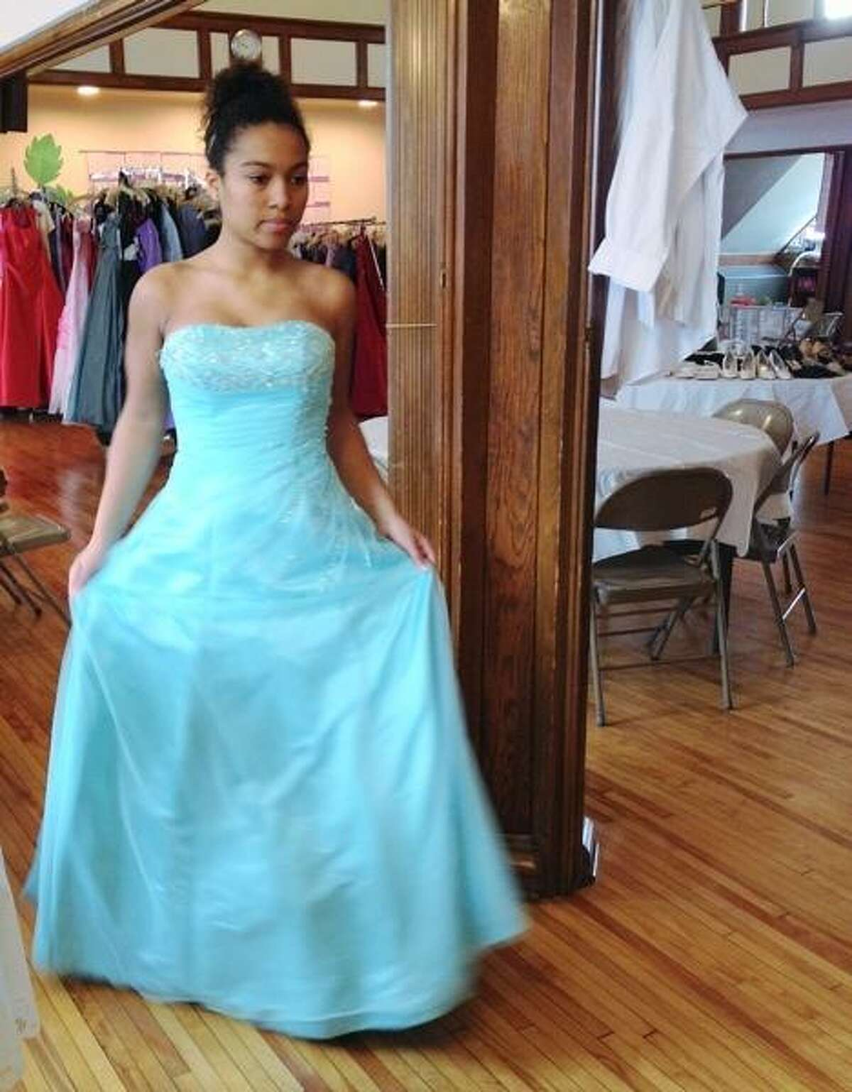 John Haeger @OneidaPhoto on Twitter/Oneida Daily Dispatch Coralie Lolliot tries on a prom dress during the First Presbyterian Church of Oneida fourth annual prom and dinner dance dress giveaway on Saturday, March 16, 2013..