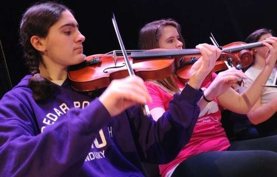 John Haeger @OneidaPhoto on Twitter/Oneida Daily Dispatch Orchestra members Brittany Papa SVCS and Thea Gamboa of Chittenango along with fellow members rehearse for the upcoming All County Music Festival Concert on on Saturday, March 16, 2013 in Canastota.
