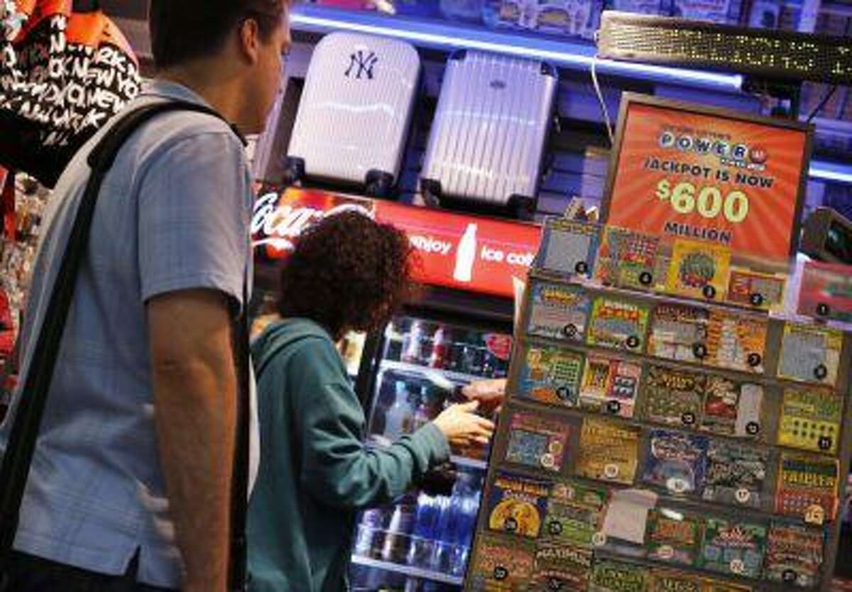 People wait in line to purchase Powerball lottery tickets at the Port Authority bus station in New York May 17, 2013.