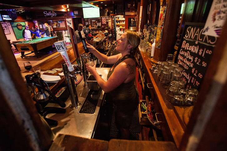 View in through the walk up window as bar tender Regynn Lesser pours a beer on tap next to the open walk out window at Smiley's Schooner Saloon, the oldest saloon west of the Mississippi (Est. 1851) in Bolinas, California, USA 23 Jul 2017. (Peter DaSilva/Special to The Chronicle)