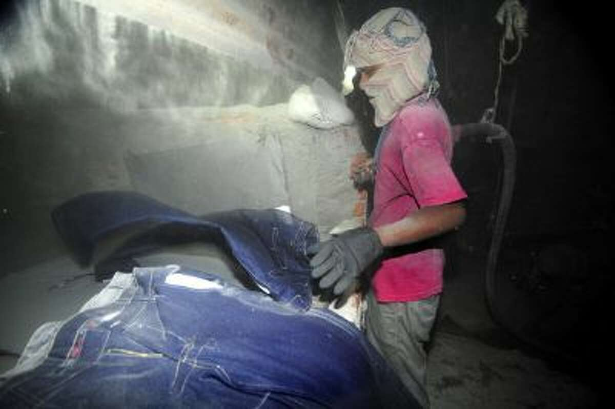 A Bangladeshi garment laborer works in a sandblasting factory in Dhaka, 2011.