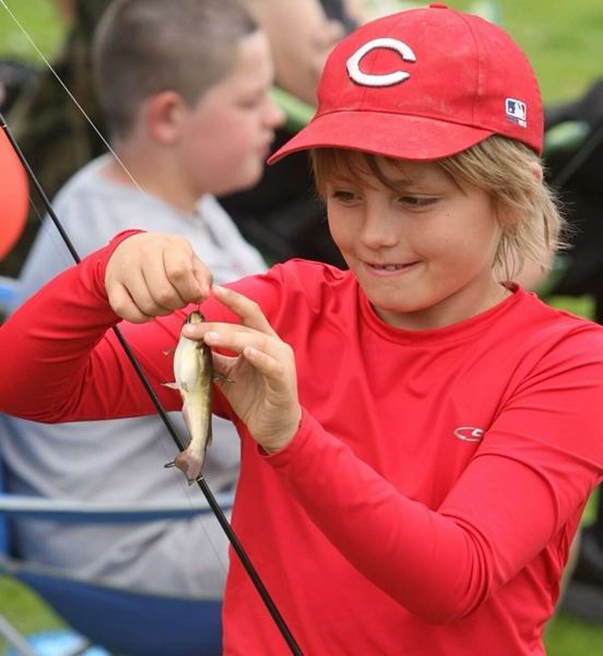 PHOTO BY JOHN HAEGER @ ONEIDAPHOTO ON TWITTER/ONEIDA DAILY DISPATCH Shane Plack ,10, of Canastota works to take a fish off the hook during the annual fishing derby in Sherrill on Saturday, May 18, 2013.