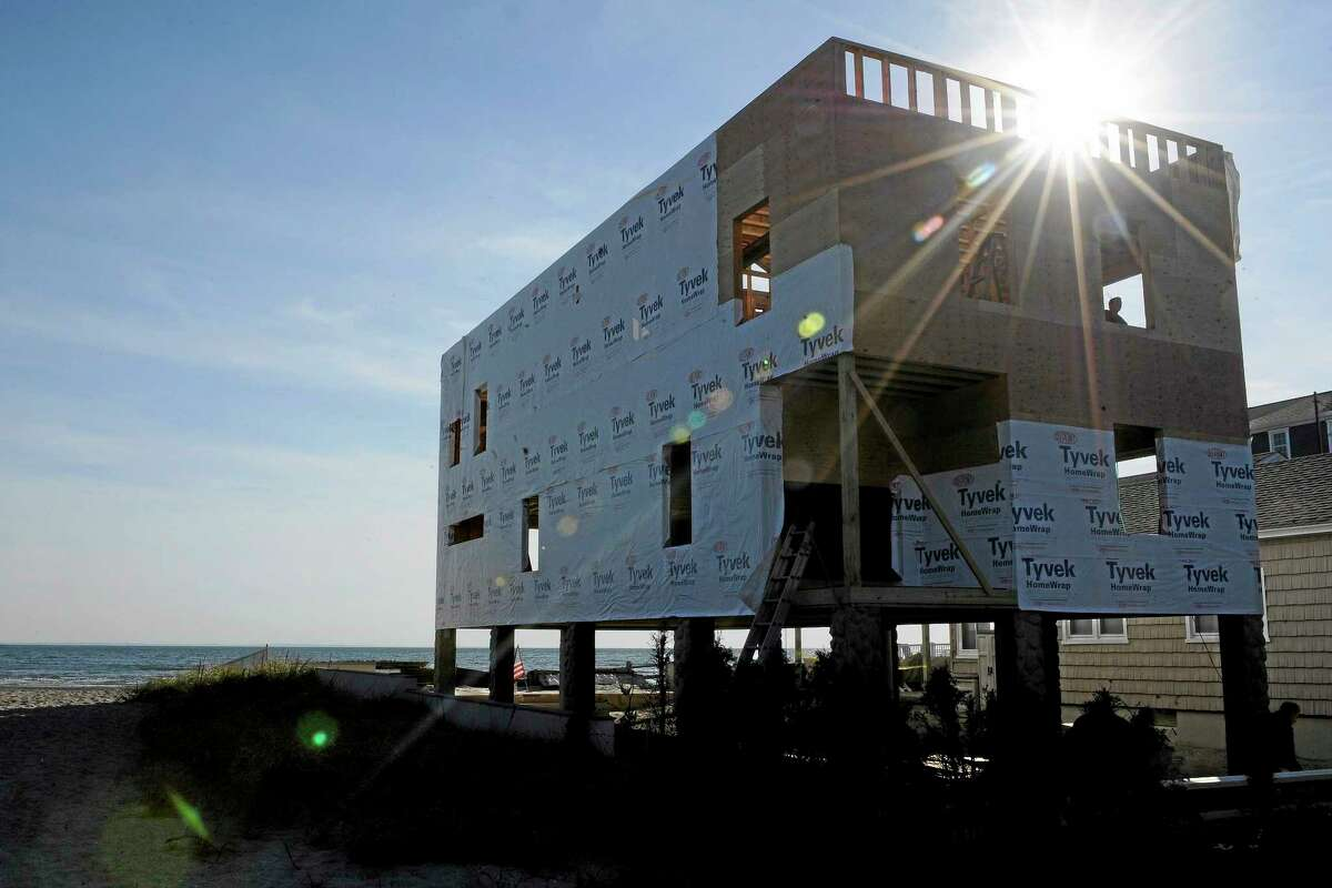 Workers rebuild a home along the shoreline, Monday, Oct. 28, 2013, in Milford, Conn. Hundreds of Connecticut residents still out of their homes since Superstorm Sandy struck. In Milford alone, at least 200 families remain displaced, officials said. (AP Photo/Jessica Hill)