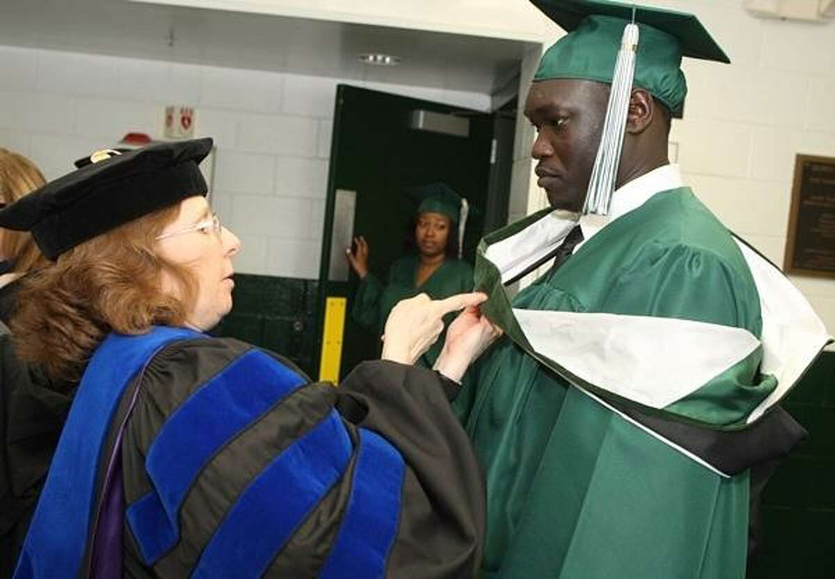 PHOTO BY JOHN HAEGER @ ONEIDAPHOTO ON TWITTER/ONEIDA DAILY DISPATCH Prof Roberta Sloan helps Deng Kiir get ready before the start of the 102nd commencement ceremony at Morrisville State College on Saturday, May 18, 2013. Deng Kiir is one of the lost boys of the Sudan, will receive his bachelor degree from the School of Business.
