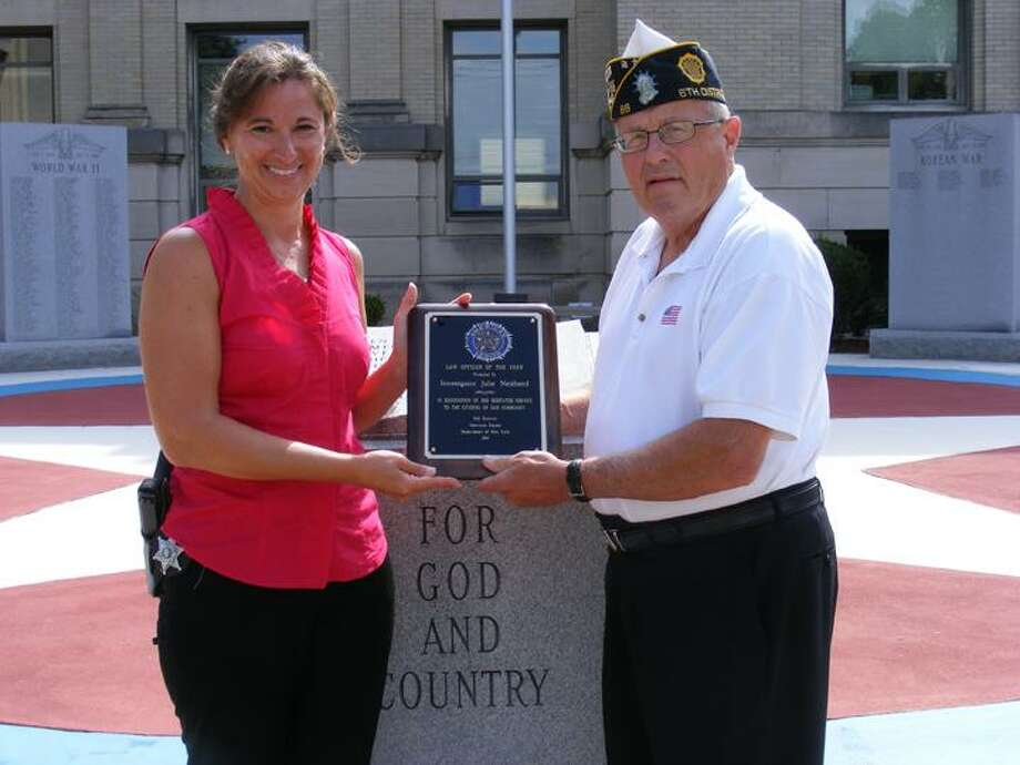 Photo Courtesy Madison County Law & Order Madison County Law & Order Chairman Joseph Barilla Sr., presents Julie Netzband with her 6th District American Legion Law Officer of the Year Award.