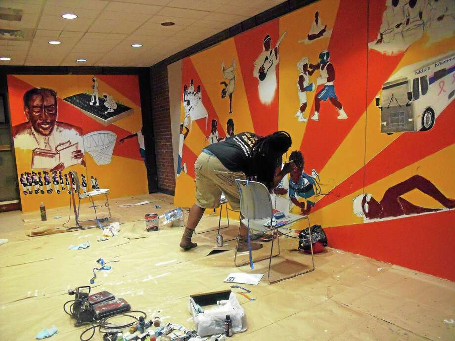 Artist Katro Storm painting the mural at the Stetson Branch Library on Dixwell Avenue in New Haven. Photo: Contributed Photo