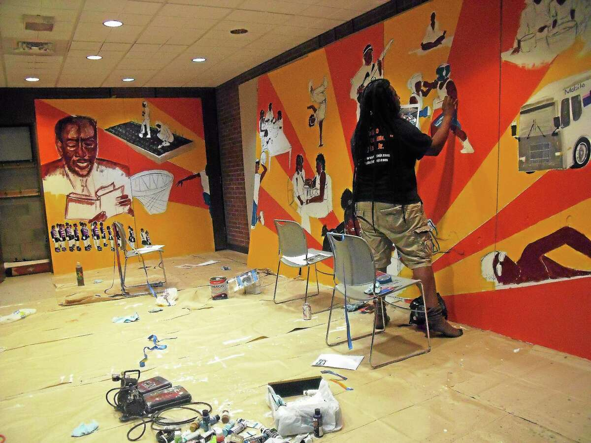 Artist Katro Storm painting the mural at the Stetson Branch Library on Dixwell Avenue in New Haven.
