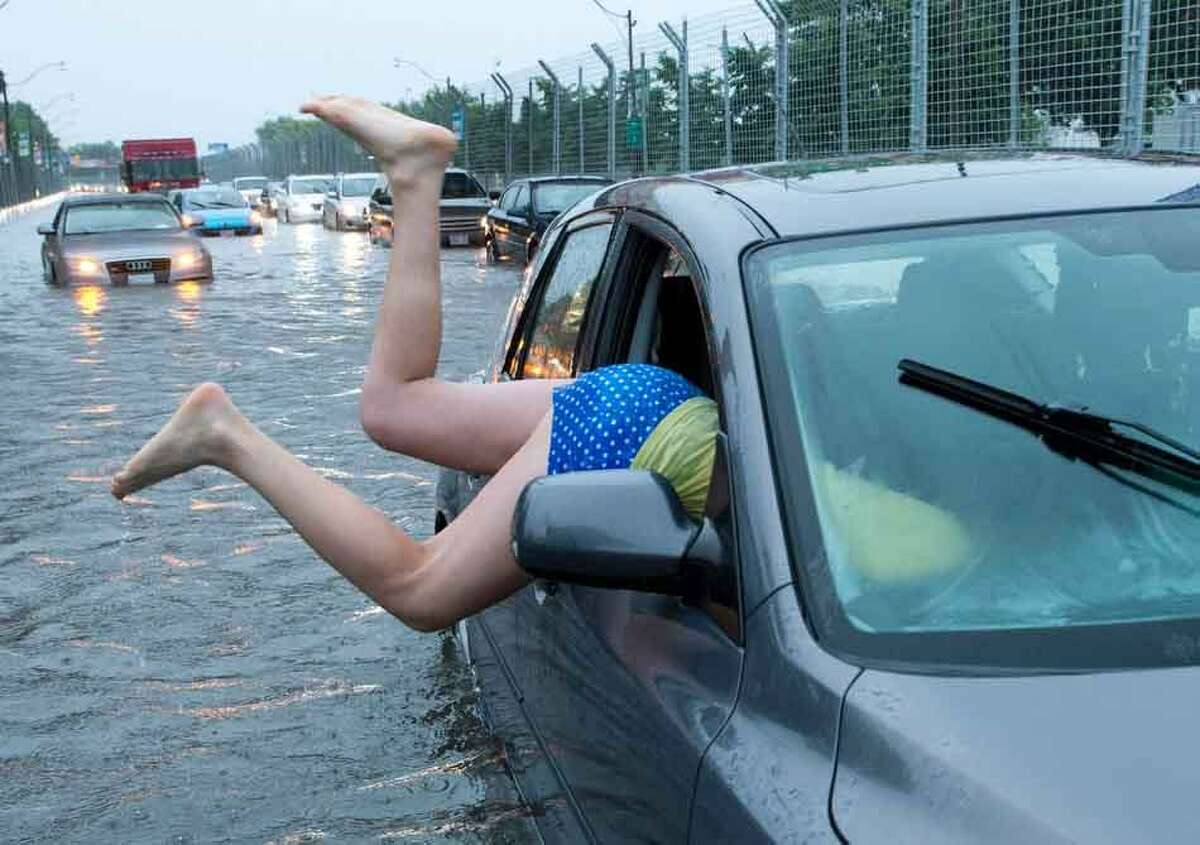 A woman gets back into her flooded car on the Toronto Indy course on Lakeshore Boulevard in Toronto on Monday, July 8 2013. (AP Photo/The Canadian Press, Frank Gunn)