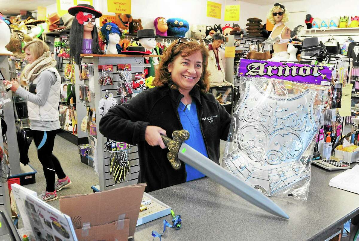 (Peter Hvizdak — Register) Julie Fowler of Guilford purchases a plastic sword and breastplate for her daughter's Joan of Arc costume Tuesday at Characters and Costumes at 260 River St. in Guilford. Fowler's daughter, a high school English teacher at the Academy of the Holy Family High School in Baltic, is wearing the costume to school on Halloween. The store is open year-round and rents and sells costumes and accessories. Holiday hours are 10 a.m. to 8 p.m. tonight, 10 a.m. to 7 p.m. Thursday and Friday and 10 a.m. to 6 p.m. Saturday.