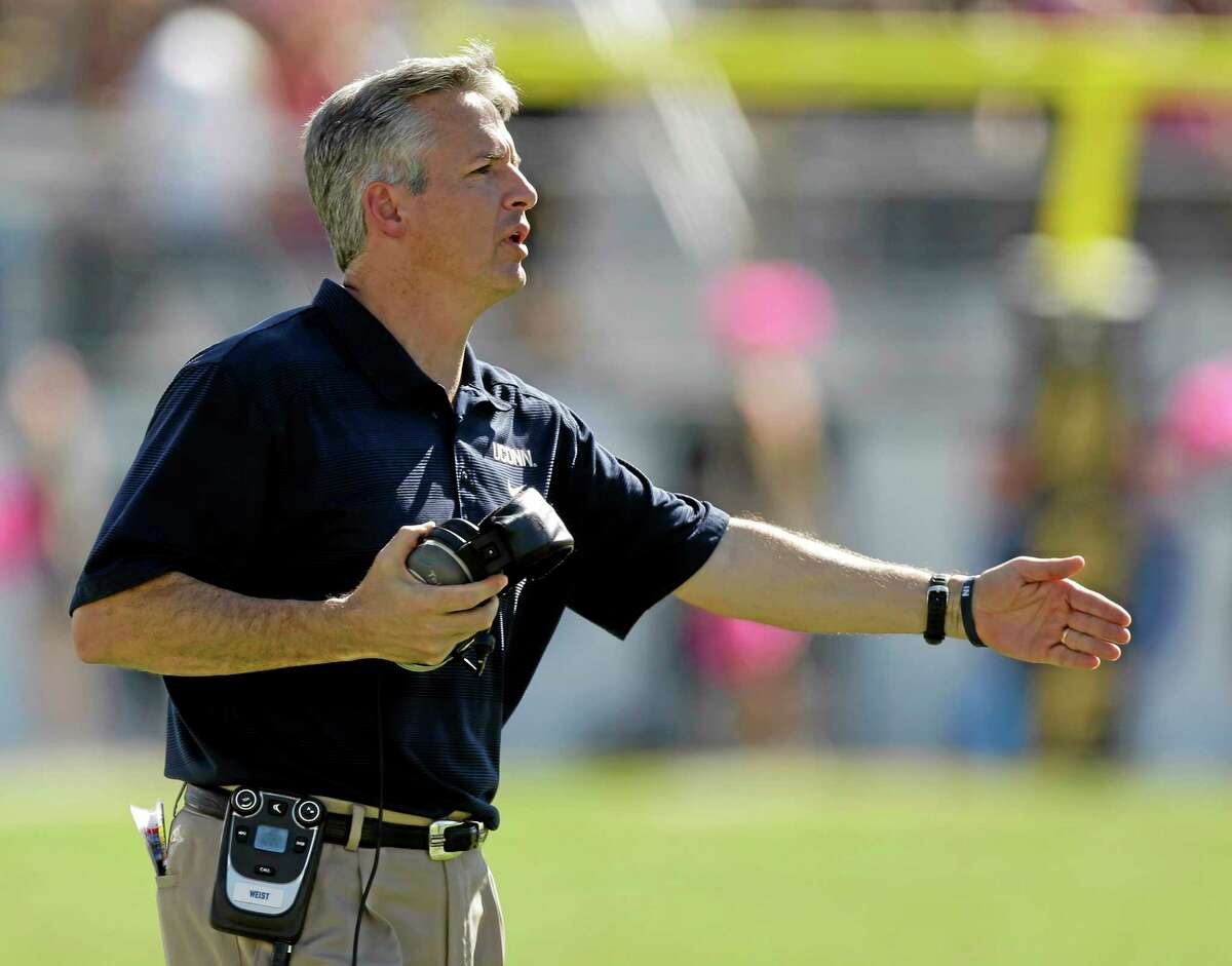John Raoux — The Associated Press UConn interim head coach T.J. Weist question a call by an official during the second half of Saturday's 62-17 loss to Central Florida.