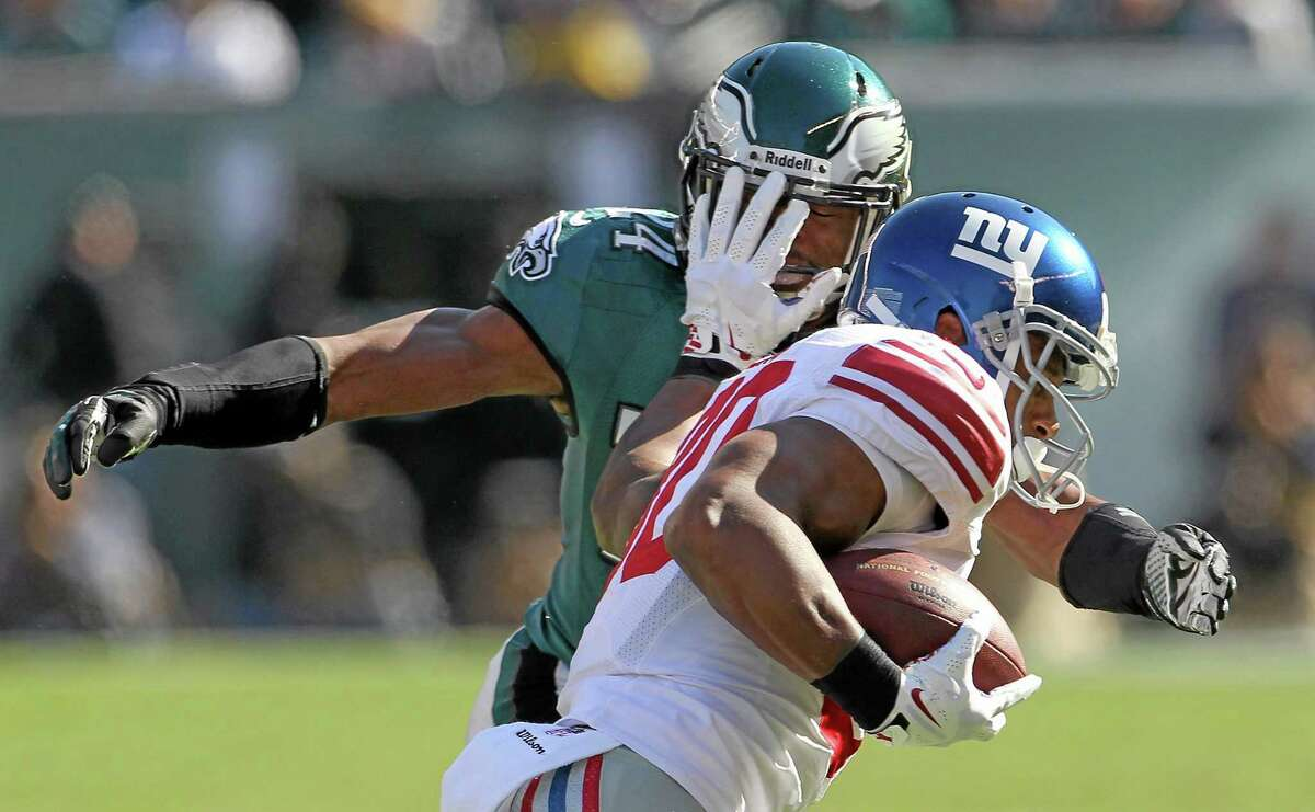 The Giants' Victor Cruz runs the ball against the defense of Eagles' Bradley Fletcher during first half of Sunday's game.