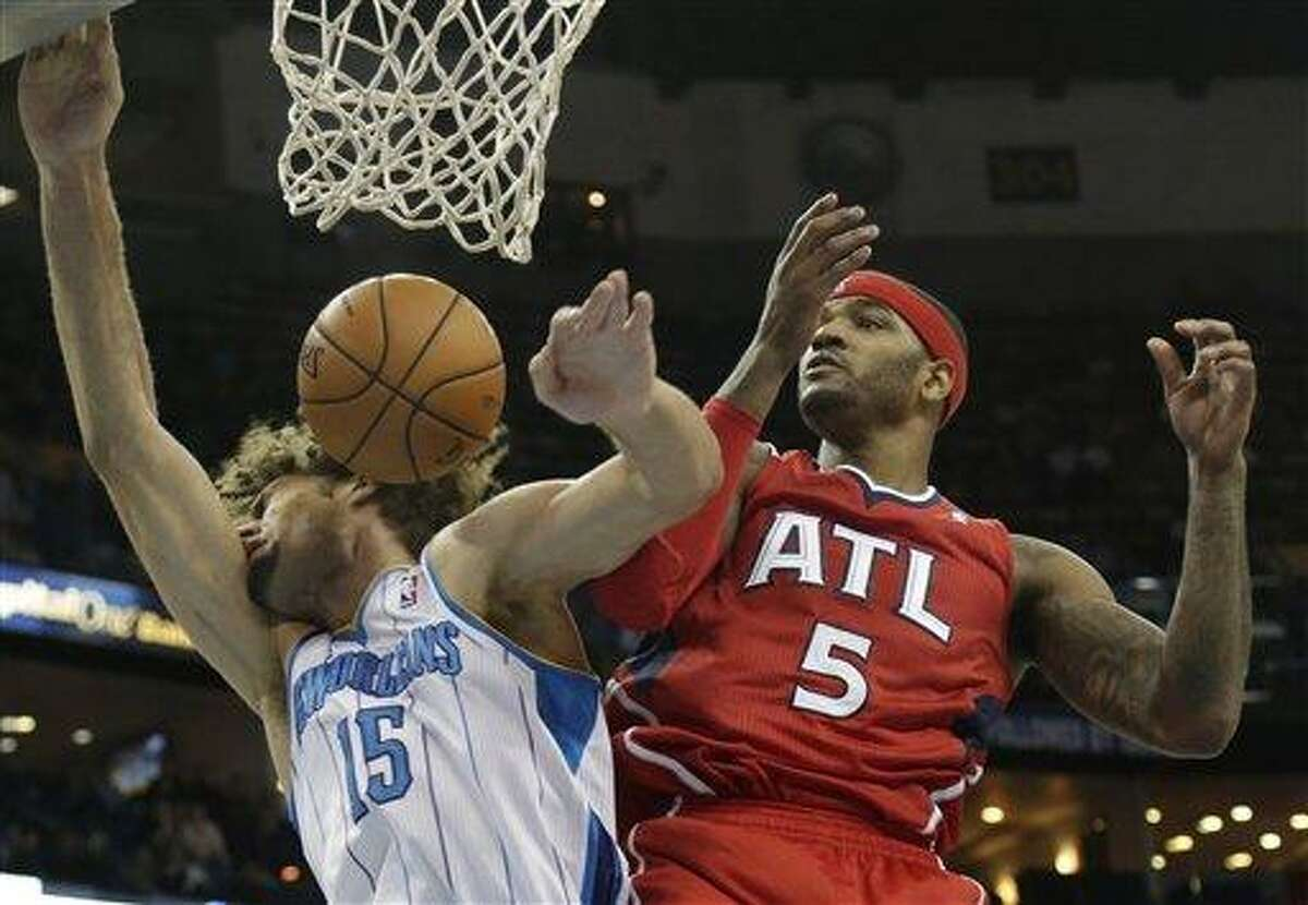 Atlanta Hawks small forward Josh Smith (5) fights for a rebound with New Orleans Hornets center Robin Lopez (15) during the fourth quarter of an NBA basketball game at the New Orleans Arena in New Orleans Tuesday, Jan. 1, 2013. Atlanta beat New Orleans 95-86. (AP Photo/Dave Martin)