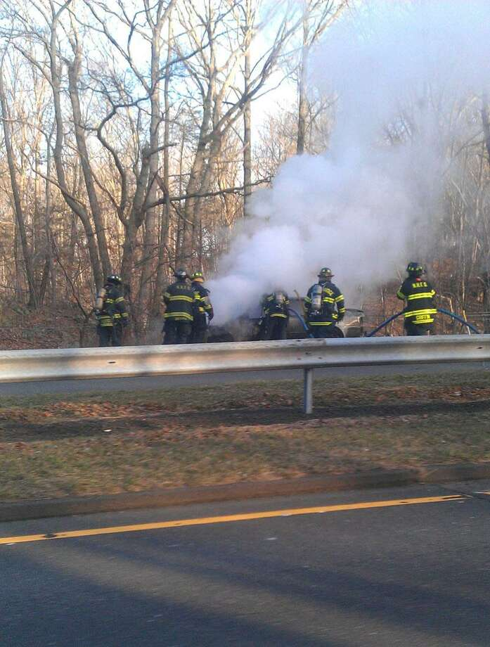Firefighters work to put out the car fire Friday on Wilbur Cross Parkway. Pam McLoughlin/Register