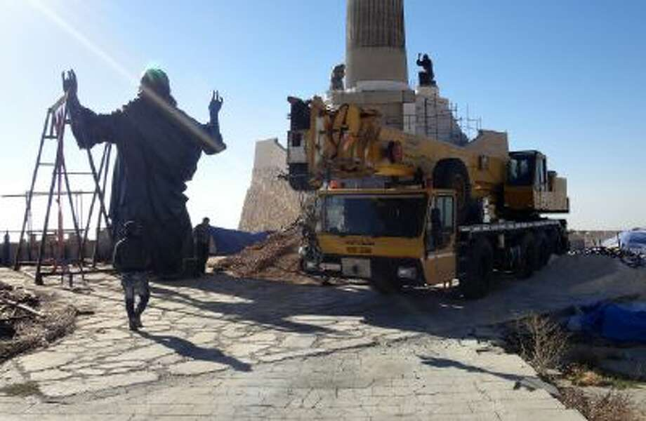 This Oct. 14, 2013 photo provided by the St. Paul's and St. George's Foundation shows workers preparing to install a statue of Jesus on Mount Sednaya, Syria.