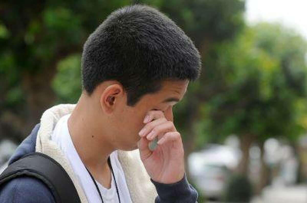 Survivor of airplane crash Kim Jeong Han 17, of Seoul, South Korea, wipes his eye as he speaks of his experience of Asiana Airlines Flight 214, while outside the Korean consulate in San Francisco, Calif., on Sunday, July 7, 2013. It was Han's first airplane ride and first time to the United States. He said he broke a toe on his left foot and was given a new pair of shoes because his were unwearable.