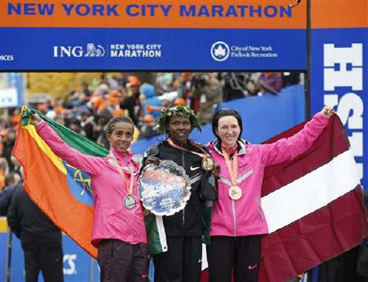 Women's winner Priscah Jeptoo of Kenya, center, second place finisher Buzunesh Deba of Ethiopia, left, and third place finisher Jelena Prokopcuka of Latvia pose with their medals after the New York City Marathon, Sunday, Nov. 3, 2013, in New York.