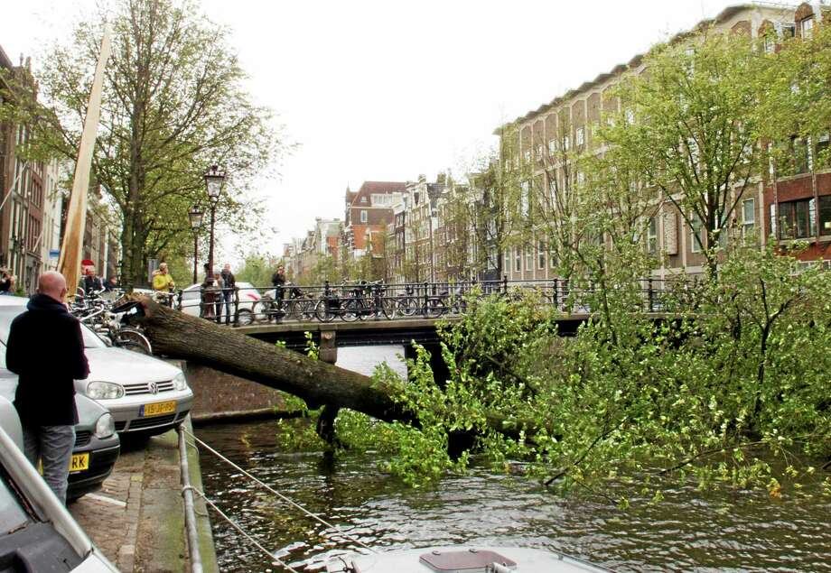 A fallen mature tree blocks the Herengracht canal in Amsterdam, Monday, Oct. 28, 2013. A major storm with hurricane-force gusts lashed southern Britain, the Netherlands and parts of France on Monday, knocking down trees, flooding low areas and causing travel chaos.  Amsterdam police said a woman was killed when a tree fell on her in the city and Dutch citizens were warned against riding their bicycles because of the high winds. (AP Photo/Margriet Faber) Photo: AP / AP