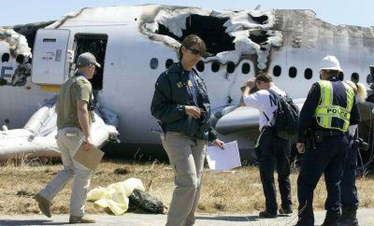 National Transportation Safety Board investigators work Sunday, July 7, 2013, on their investigation into the cause of Saturday's crash of Asiana Flight 214, a Boeing 777 aircraft, at San Francisco International Airport. (NTSB)
