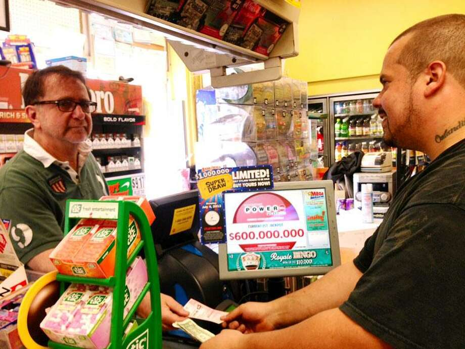 New Haven resident Orlando Rolon purchases a Powerball ticket Friday from Gerry Katz, owner of the Shell Food Mart on Willow Street in New Haven. Rich Scinto/Register