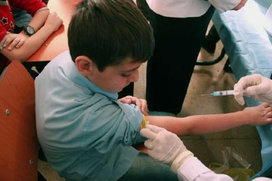 In this Oct. 20, 2013 photo released by UNICEF, a Syrian student receives a vaccination as part of a UNICEF-supported vaccination campaign at a school in Damascus, Syria.