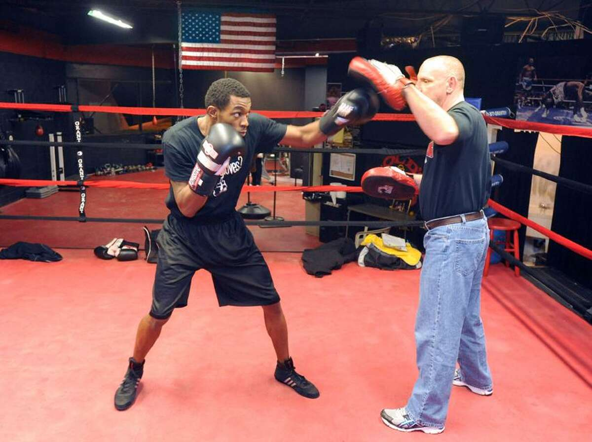 Boxer Jimmy Williams of West Haven does pad work with head trainer John Spehar of New Haven, at New Haven Boxing in North Haven. Mara Lavitt/New Haven Register1/15/13