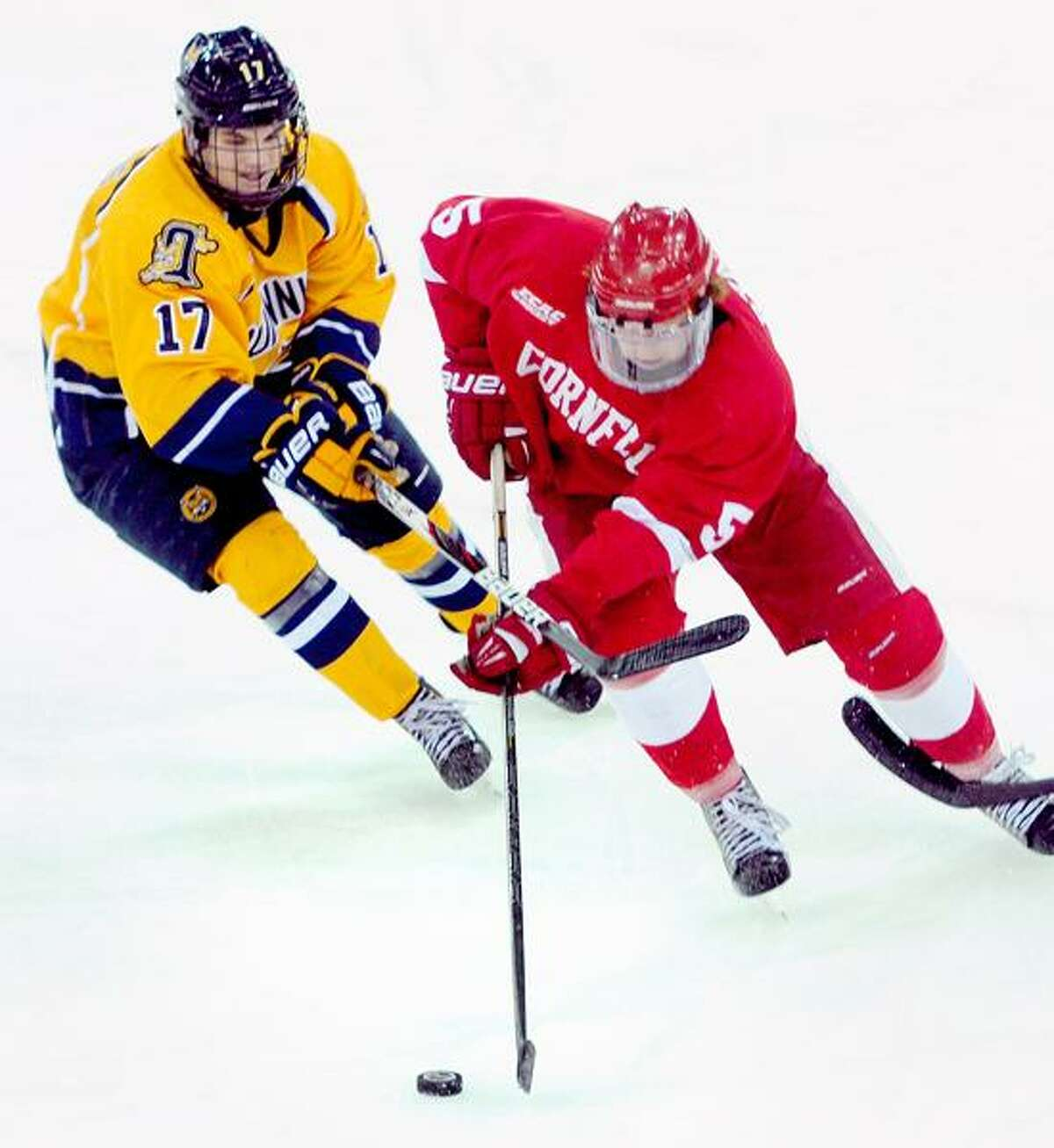 Jeremy Langlois (left) of Quinnipiac and Joakim Ryan (right) of Cornell fight for the puck in the second period during a ECAC quarterfinal contest on Friday. Arnold Gold/New Haven Register