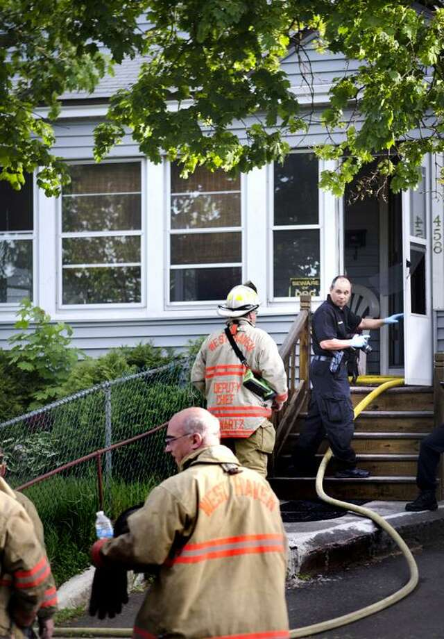West Haven-   A police photographer enters the home, on First Street, where a fatal fired occured.    Melanie Stengel/Register